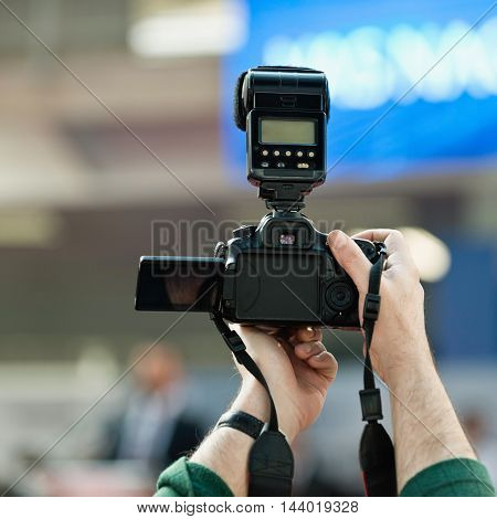 Photographer holding camera on press conference, toned image, close up, unrecognizable people