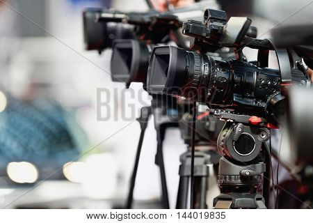 Television camera on press conference, toned image, close up, unrecognizable people