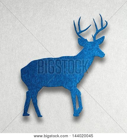 Side view of a symbolic Christmas reindeer with antlers in a textured blue silhouette cutout design with shadow on grey with copy space for your seasonal greeting