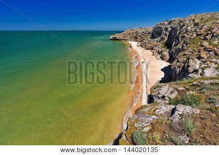 stone rock on a sandy seashore and blue sky