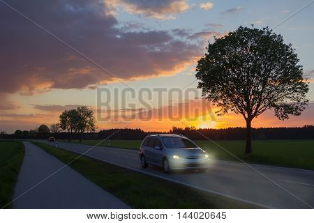car trip at dawn with dim light countryroad in sunset landscape low visibility