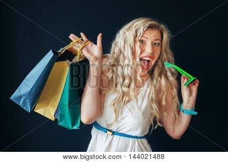 beautiful curly blonde woman in glasses with new purchases. The concept of shopping
