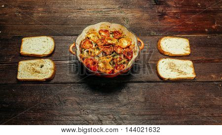 Pan with baked ratatouille - traditional French vegetarian dish - and toasts on the table