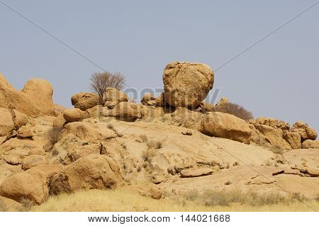 A circular Boulder resting on the brow of a hill in Namibia
