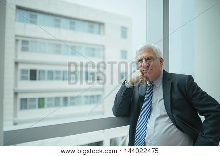 Experienced businessman standing at window in modern office