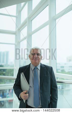 Portrait of smiling mature businessman with laptop