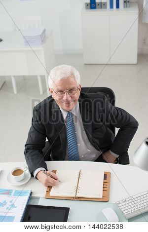 Smiling mature businessman writing plans for the day in notepad
