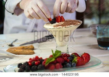 Hands touch pieces of berries. Biscuits and glass with dessert. Fresh strawberries for tiramisu. Chef is decorating sweet dish.