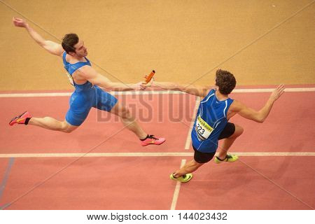 LINZ, AUSTRIA - FEBRUARY 22, 2015: Manuel Prazak (#235 Austria) and Thomas Wannasek (#223 Austria) compete in the men's 4x200m relay event in an indoor track and field event.