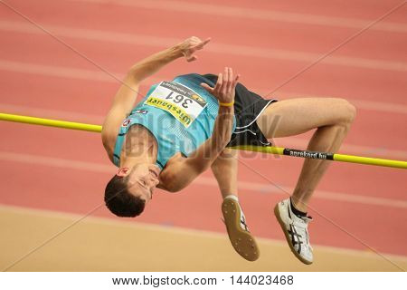 LINZ, AUSTRIA - FEBRUARY 22, 2015: Josip Kopic (#361 Austria) competes in the men's high jump event in an indoor track and field event.