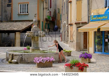 VALENSOLE, FRANCE - JULY 5. 2016: Young woman refreshing at central square with fountain at day time