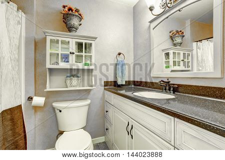 Small Bathroom Interior With White Cabinets, Granite Counter Top And Toilet.