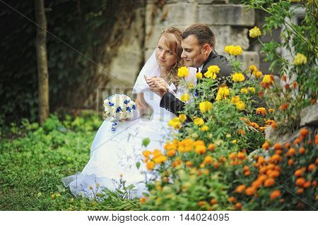 Newlyweds Siting Near Flowers And Holding Hands