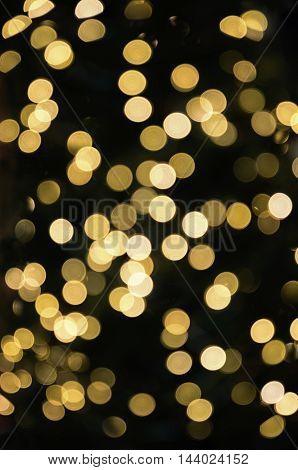 festive blurry golden flares on black background
