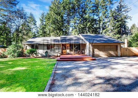 Grey House With Wooden Trim And Gravel Walkway. Curb Appeal