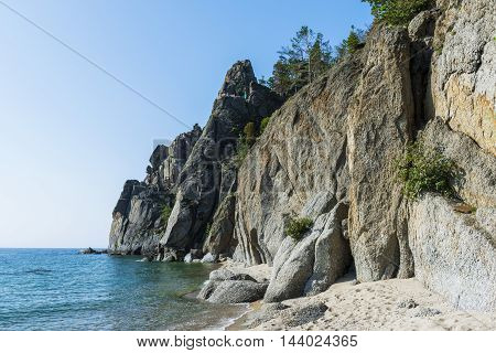 High cliffs surrounded by cozy, sandy beaches on the coast of lake Baikal.