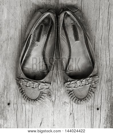 old worn women's shoes made of genuine leather on old gray wooden board with cracks. top view close-up. black and white photo