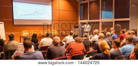 Speaker giving a talk in conference hall at business event. Audience at the conference hall. Business and Entrepreneurship concept.