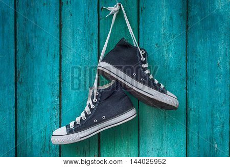 pair of blue men's sports sneakers hanging from a nail on the wall of the old shabby green horizontal composition