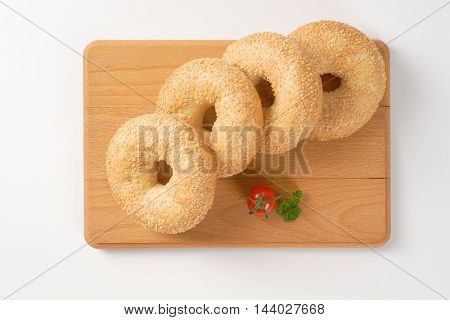 fresh bagels with sesame seeds on wooden cutting board