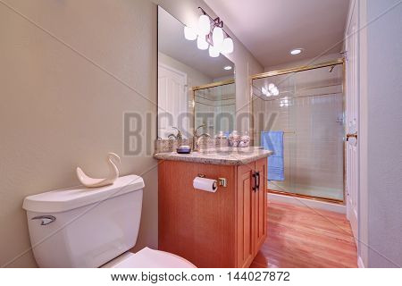 Glass Shower And Vanity Cabinet In Bright Bathroom