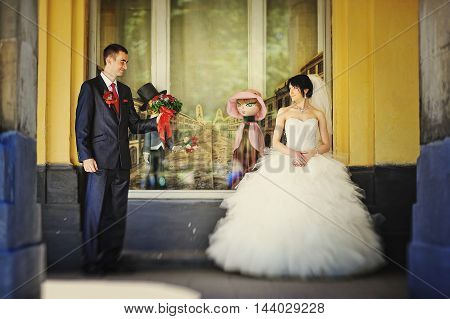 Just Married Couple Around Windows With Two Funny Dolls