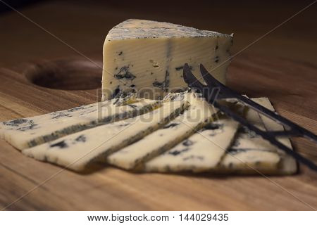 Blue cheese close up on an old wooden board and a knife Selective focus