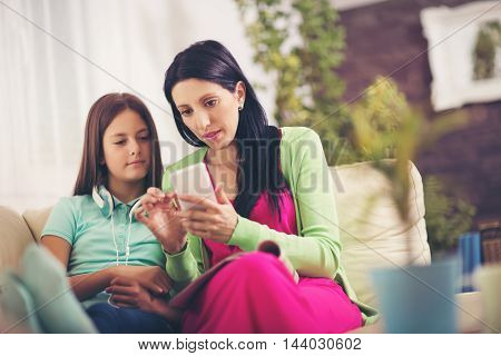 Happy mother and her cute teen daughter are looking at mobile phone while sitting on sofa at home.