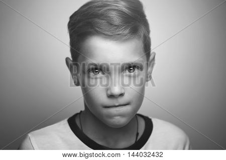 Serious handsome teenage blond boy with stylish haircut and bright clever eyes black and white retro studio portrait.