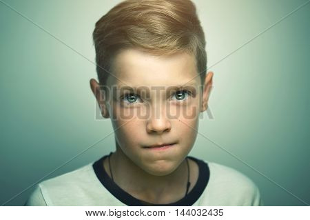 Serious handsome teenage blond boy with stylish haircut and bright clever eyes studio portrait.