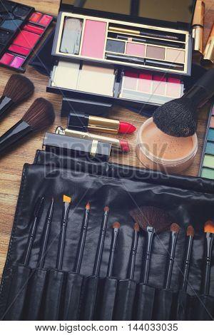 Collection of black make up brushes, lipsticks, maskara, eye shadows and powder, retro toned