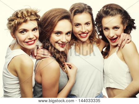 Fashion portrait of four stylish sexy hipster girls best friends, over gray background. Happy time for fun.