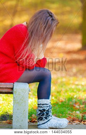 Loneliness negative emotion concept. Young sad stressed woman sitting in autumnal park.