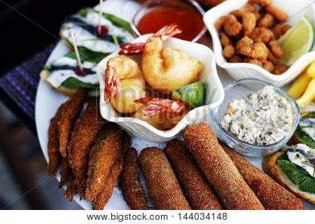 Nibbles sharer plate. King Prawns, Baby shrimps in bread crumbs, anchovies on toast bread , fish fingers, crab sticks in bread crumbs, sardines in bread crumbs. At the restaurant cafe bistro pizzeria terrace