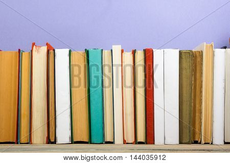 Colorful composition with vintage old hardback books, diary on wooden deck table and purple background. Books stacking. Back to school. Copy Space. Education background