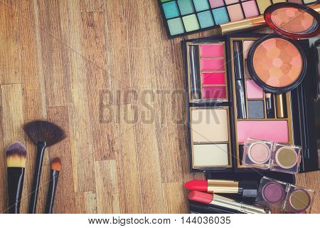 Frame of brushes, lipsticks, maskara, eye shadows and powder on wooden table, top view, retro toned
