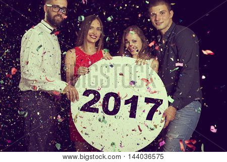 Group of friends having fun celebrating New Year's Eve and holding cardboard circle with 2017 written on it