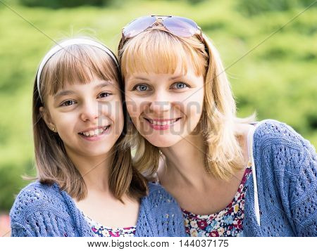 Happy family outdoors in summer day. Mother Day. Portrait of mother and daughter smiling into the camera lens. Woman with child having fun together during walk in the park.