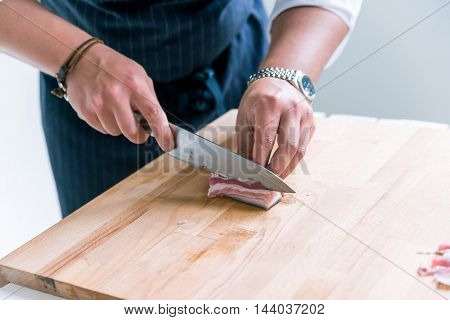 Closeup image hands and knife slicing ham