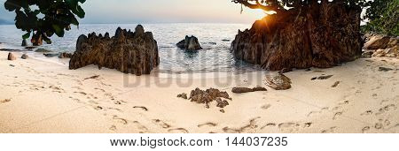 Beautiful seascape. Sea sand with footsteps and rock at the sunset. Nature composition. Thai beach in sunset time in Koh Chang island Thailand.