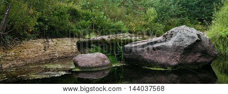 landscape large boulders lying in middle of quiet river shoaled