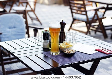 Pint of beerwit peannuts and chips on the violet napkin and wood table at the restaurant cafe bistro pizzeria terrace