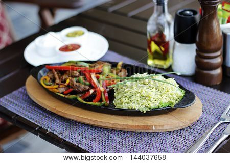 Fajitas with Mexican Rice on the black and wood plate and napkin. At the restaurant cafe bistro pizzeria terrace. Wood table.