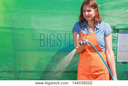 Gardening. Woman in orange apron holds the sprinkler hose for irrigation plants watering the garden outdoor