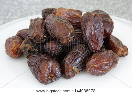 a white dish of fresh healthy dates