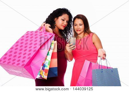Beautiful happy friends women standing together with colorful shopping bags looking at mobile phone device consumer lifestyle concept.