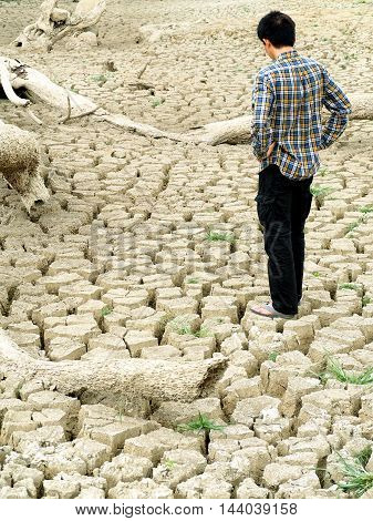 The farmer standing on mud crack in dry season