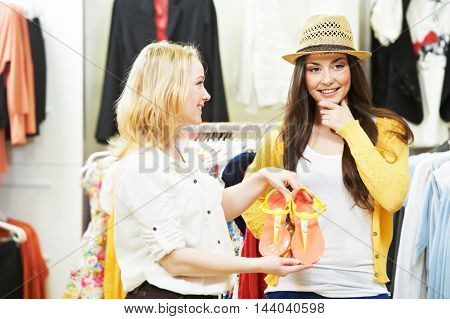 two Young women at apparel clothes shopping