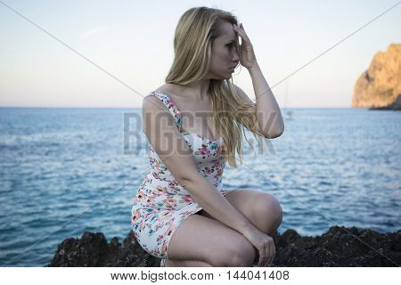 pretty blonde dressed in floral dress in a cove on the island of Mallorca next to the Mediterranean Sea