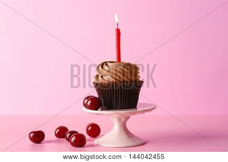 Tasty chocolate cupcake with berries on pink background